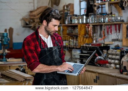 Carpenter working on his computer on his workshop