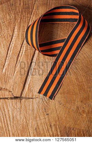 Victory day: St. George ribbon on wooden background in the form of figures 9