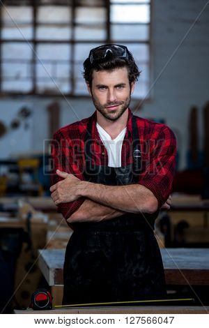 Carpenter smiling and crossing arms on his workshop