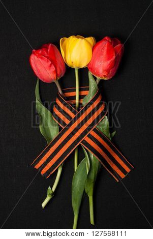 George ribbon red and yellow tulips on a black background