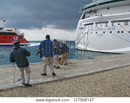 ISLAND OF MYKONOS, CYCLADES, GREECE - SEPTEMBER 12, 2009: Cruiser workers are pulling the ropes of giant cruiser ship Brilliance Of The Seas.