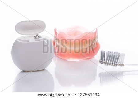 Teeth Model With Toothbrush And Dental Floss On White Background