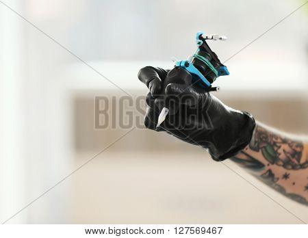 Man's hand holding tattoo machine on blurred background