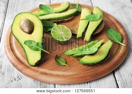 Slices of fresh avocado on wooden cutting board closeup