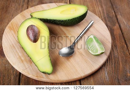 Fresh avocado with lime on wooden background
