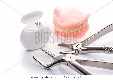 Teeth Model With Dental Floss And Forceps On White Background