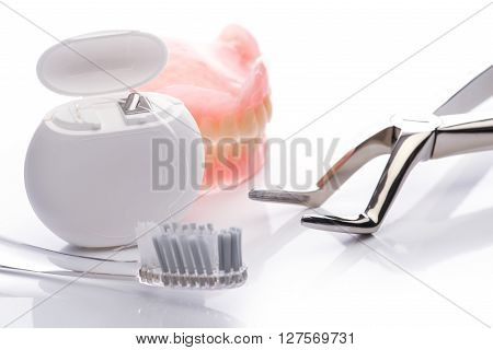 Teeth Model With Dental Floss, Toothbrush And Forceps On White Background