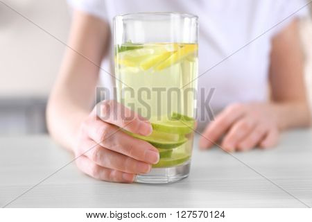 Female hand holding glass of lemonade closeup