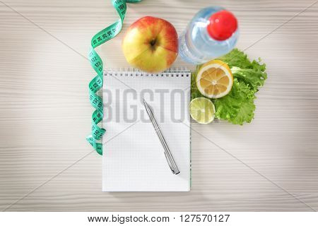 Blank notebook, measuring tape and healthy food on wooden table, top view