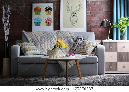 Design interior of living room with grey sofa and bouquet of flowers on table
