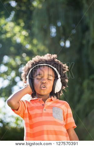 Boy is listening music in a park
