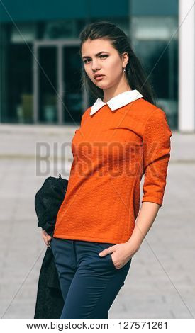 Young woman in orange jersey. Outdoor photo in the city.