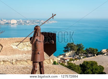 The rusty knight in the Santa Barbara castle and view of Alicante coast. Santa Barbara is a main landmark in the Alicante city. Costa Blanca. Spain