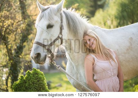Young blonde woman posing outdoor with white horse. Rider and her horse outdoor.