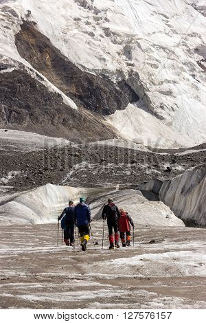 Group of Mountain Climbers with High Altitude Boots and Clothing Crossing Ice Section During Ascent of Alpine Expedition in Asia Mountain Area Vertical