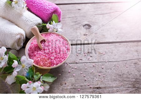 Spa or wellness organic product. Pink sea salt in bowl towels and flowers in ray of light on aged wooden background. Selective focus. Place for text.