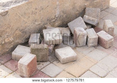 Pieces Of Old Paving Slabs Lie In A Concrete Block On The Pavement