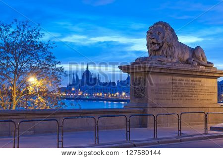 Budapest, Hungary - April  17, 2016:  Parliament Building and  Lion of Chain Bridge taken from the Buda side, early in the morning.