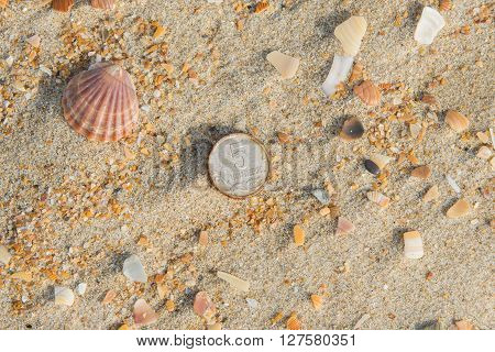 Rusty Nickels Lying On The Sand On A Sea Beach