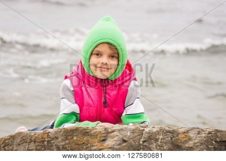 Warmly Dressed Girl Looks Out From Behind A Rock Against The Backdrop Of The Sea On A Cold Cloudy Da