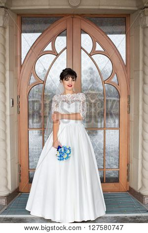 Bride holding bouquet, smiling at the camera on a rainy day