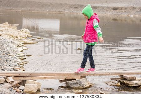Little Girl Gently Moved Across The Creek On The Board