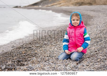 Five-year Girl Sits On A Pebble Beach In The Warm Bright Clothes On A Cloudy Day With A Smile Looks