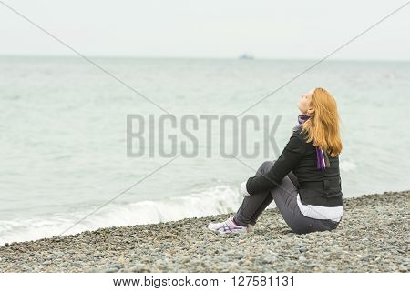 Young Girl Sitting On A Pebble Beach By The Sea Face To The Sea Breeze On A Cloudy Day