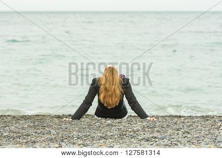 She Sits Back On A Pebble Beach By The Sea On A Cloudy Day, His Head Thrown Back