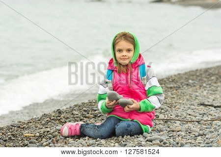 Seven-year Girl Sitting On A Pebble Beach In The Warm Clothes And Looks In The Frame
