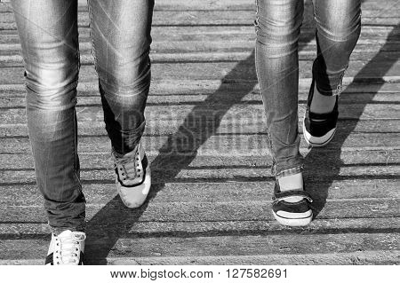 Woman jeans and sneaker shoes on wooden background, black and white photo