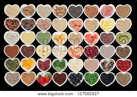 Large health and body building high protein super food in heart shaped bowls with meat, fish, supplement powders, seeds, cereals, grains, fruit and vegetables.