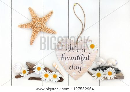 Its a beautiful day distressed heart shaped sign with daisy flowers, driftwood,  starfish and sea shells over white wooden background.