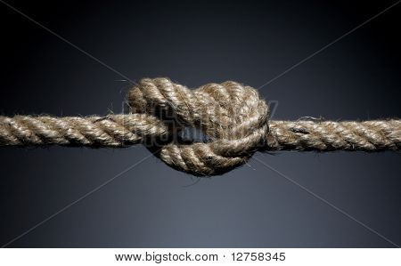 Frayed rope knot on a dark background