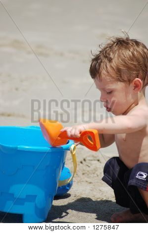 Little Boy Building A Sand Castle