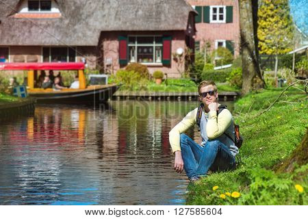Tourist with a backpack sitting by the canal in Dutch picturesque village Giethoorn