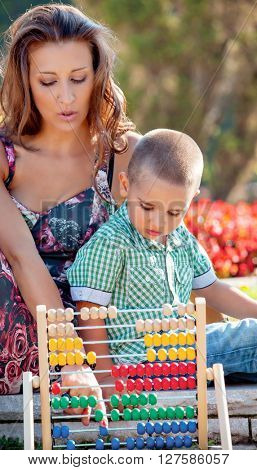 Mother teaches her son mathematics in the summer park on colorful wooden abacus.