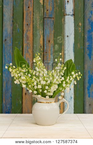 bouquet of lilies of the valley flowers with green leaves in a white jug on a background of wooden boards with remnants of old paint. with space for posting information