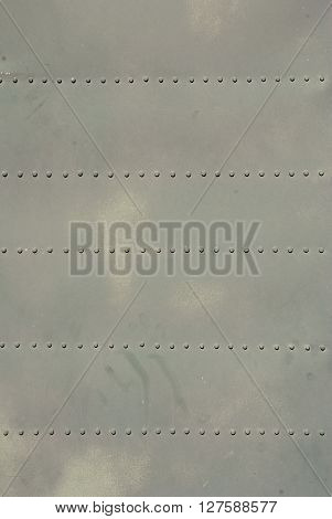old rough steel plate with rivets beige color