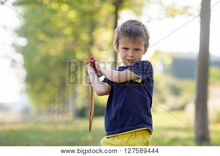 Angry little boy holding sword glaring with a mad face at the camera outdoors in the park