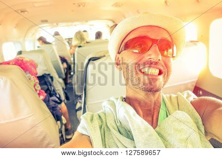 Man travel selfie inside small plane at sunset light - Cheerful tourist taking self photo with mobile phone into airplane - Concept of happiness and holidays - Vintage filter soft focus due sun halo