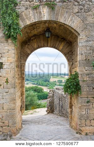 Arched doorway in a medieval stone wall in the Tuscan village of Monteriggioni Italy. Concepts could include travel architecture European heritage others.