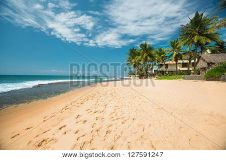 Tropical sandy beach with palm trees at sunny day. South of Bali, Jimbaran beach