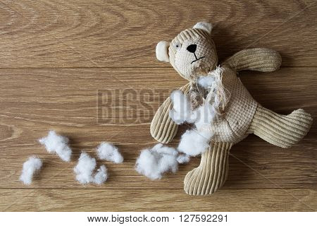 A sad, abandoned child's teddy bear with his stuffing removed and laying on a cold, wooden floor.