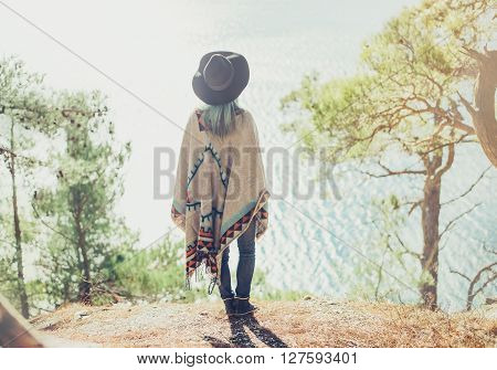 Fashionable young woman wearing in hat and poncho standing on steep coast in the forest among pine trees and looking at sea rear view
