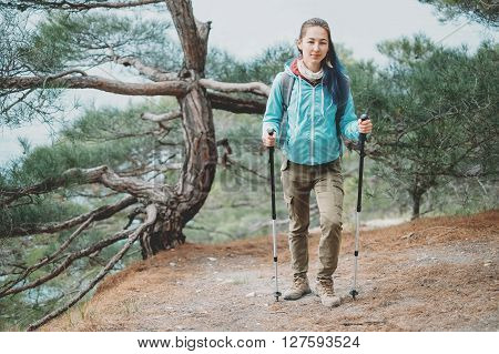 Hiker young woman with trekking poles walking in the pine forest