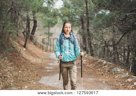Traveler young woman with trekking poles walking on footpath among pine trees in the forest
