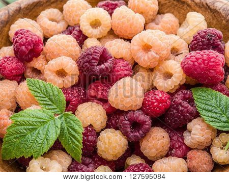 Raspberries in the wooden bowl on the table.
