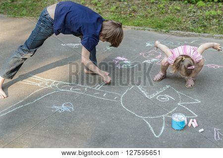 Sibling children are playing during sidewalk chalking on asphalt surface