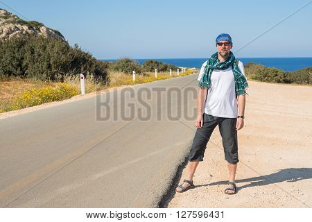 Bearded man wearing a scarf traveling hitchhiking is on the road to the sea. Sunny morning on Cyprus.
